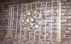 Balcony with a round centre panel showing a bird on the branch. of a grapevine